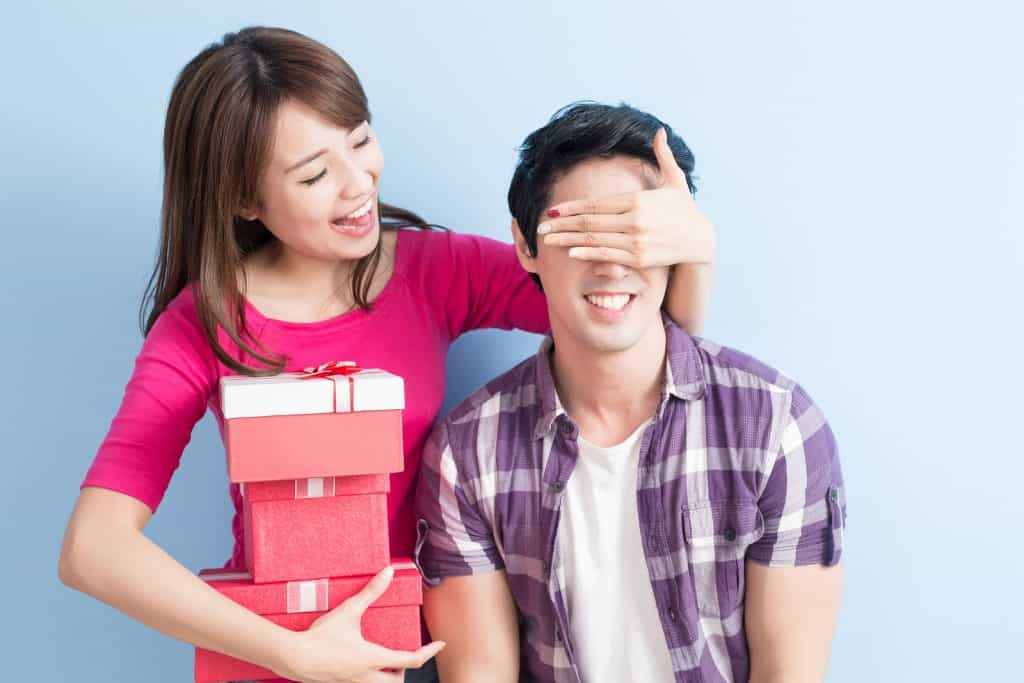 Woman in a pink shirt holding 3 boxes of presents covering the eyes of a man wearing a white t-shirt and purple shirt over it