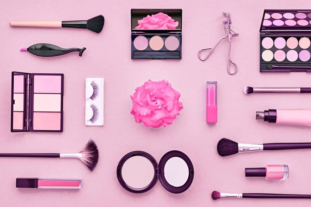 Various kinds of womens makeup on a pink table with a flower in the center
