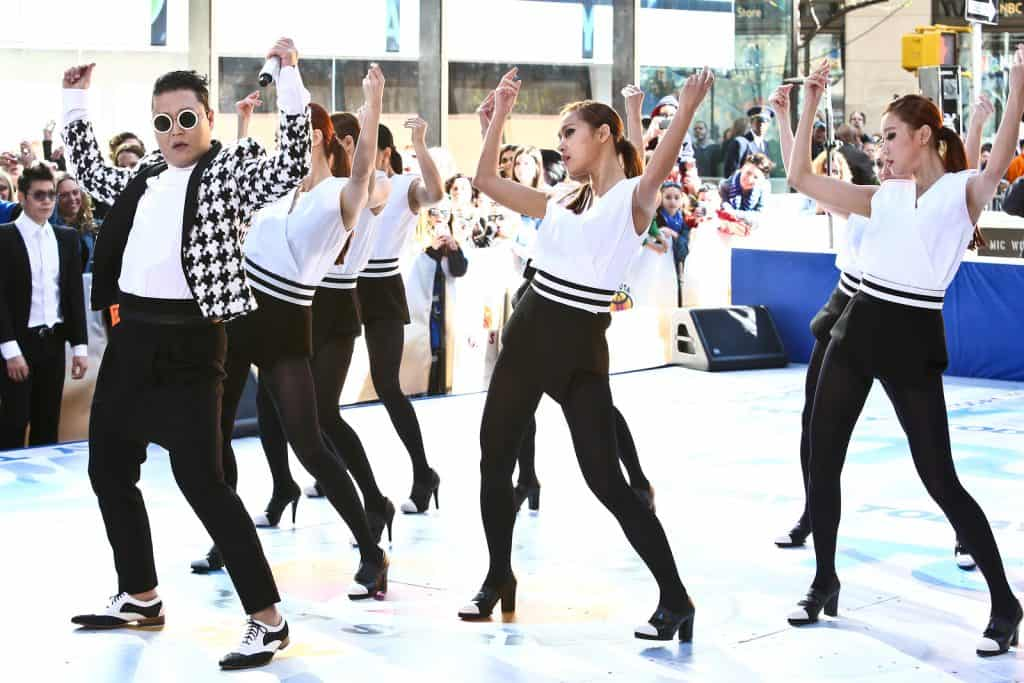 Psy and other females dancers wearing black and white with their arms up