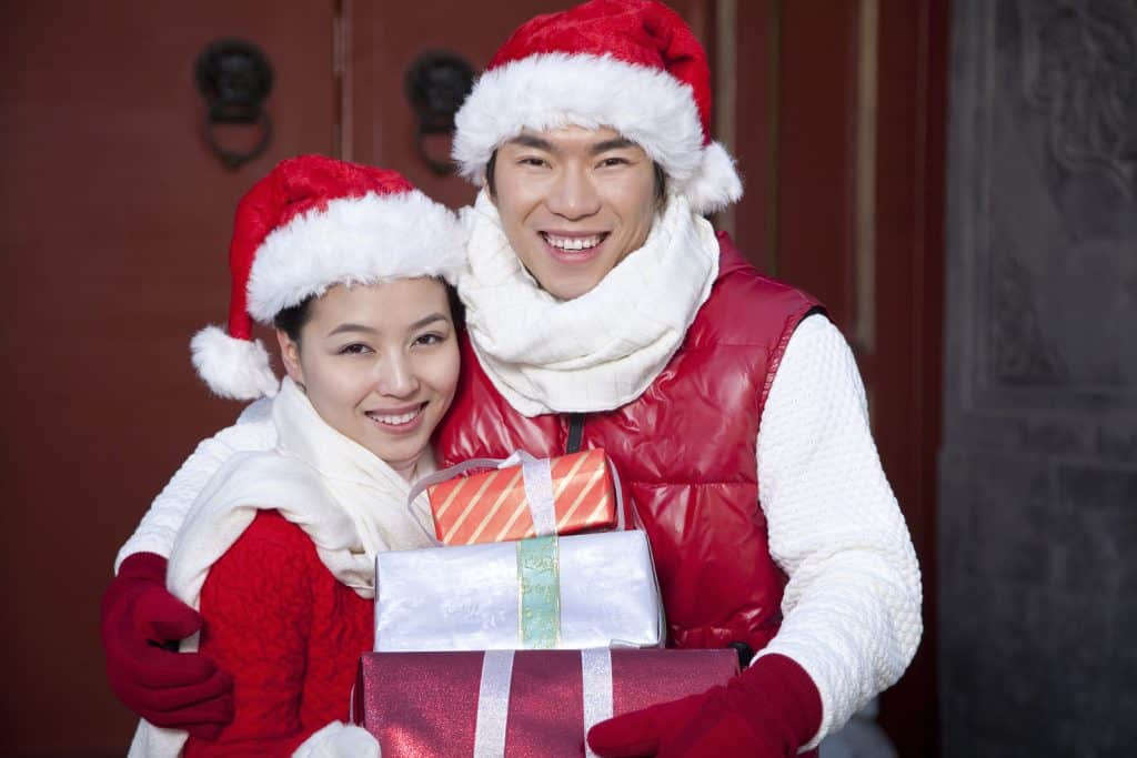 Man and woman wearing santa hats and festive clothes holding presents