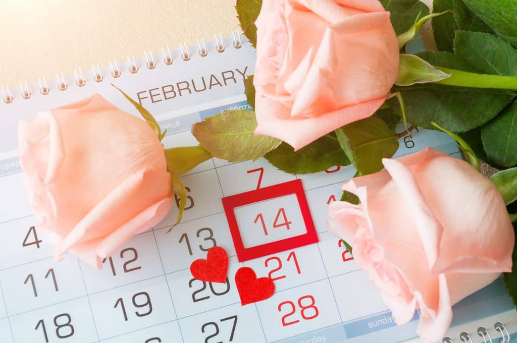 White spiral calendar with a red box around February 14th and pink roses on top of ot