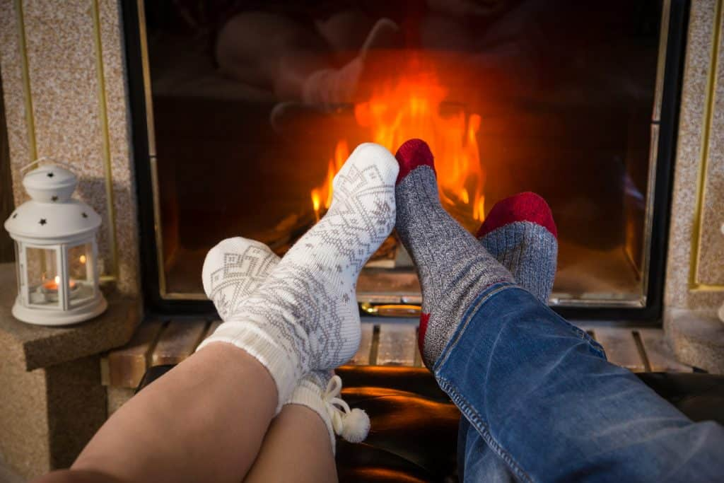 Couple wearing socks putting their feet near a fireplace