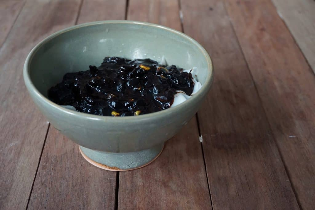 Black berries in a green bowl on a table