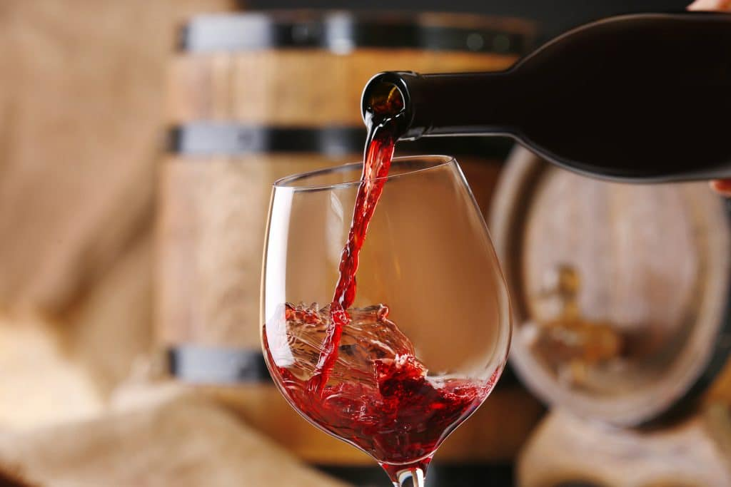 A glass of red wine being poured with wine barrels in the background