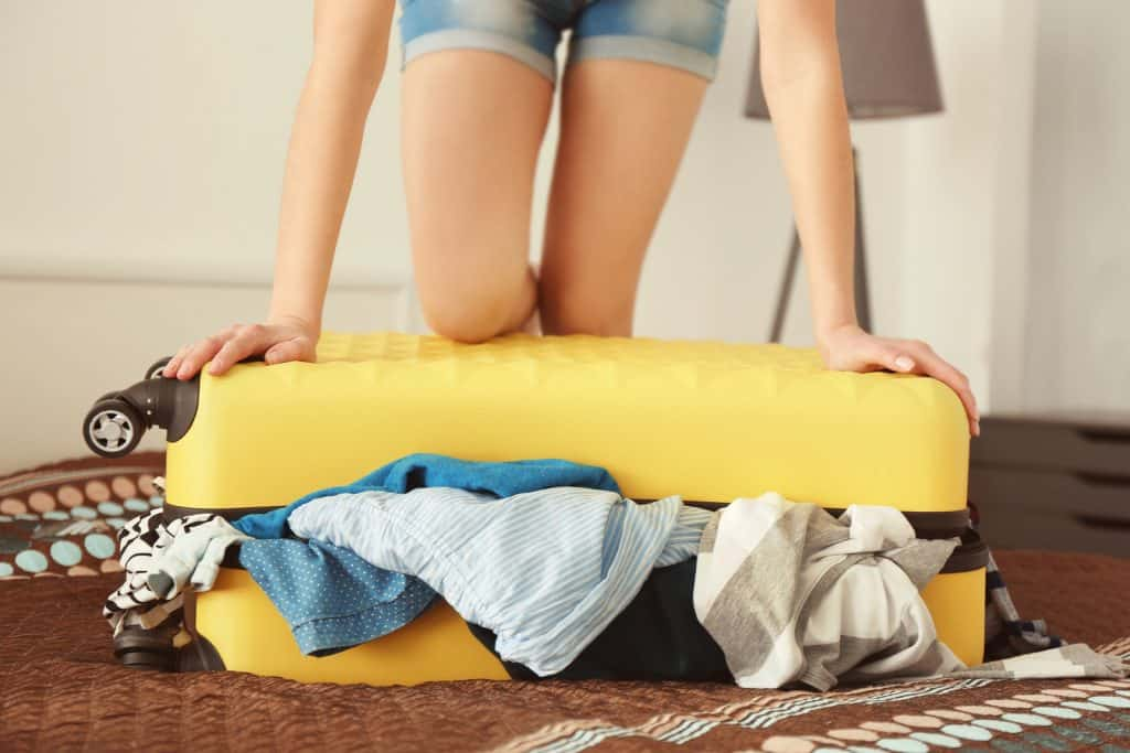Girl packing a yellow overstuffed suitcase and putting her knee on it to try to close it