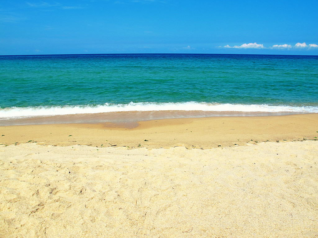 Picture of a beach with clear waters, brown sands, and clear skies