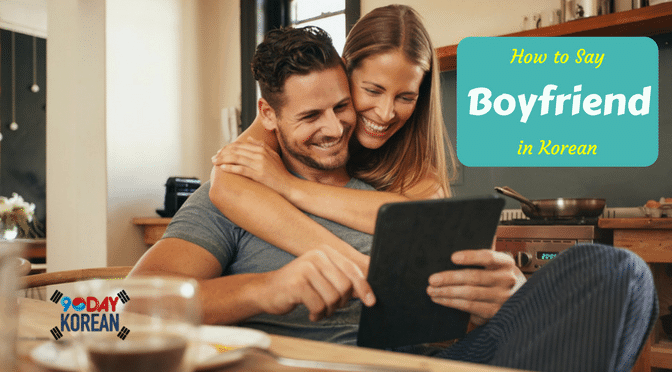 A woman back hugging her boyfriend while they are looking at a tablet