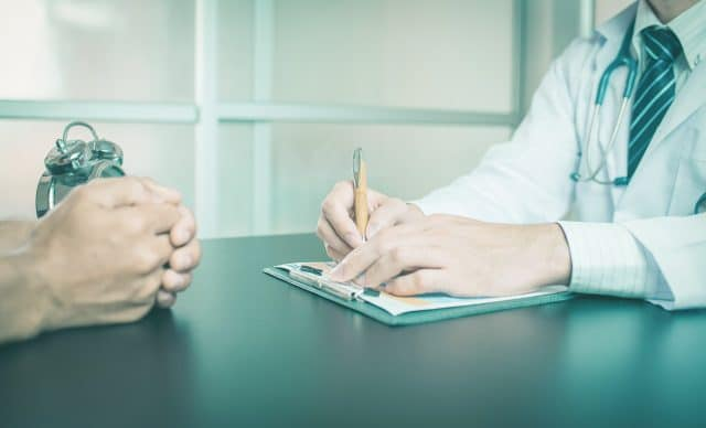 Doctor in a white coat writing in a file while talking to a patient
