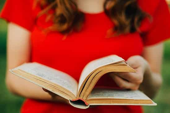a woman in a red dress reading a book