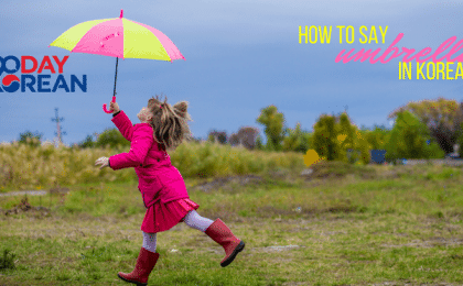 A little girl running in a field with a colorful umbrella