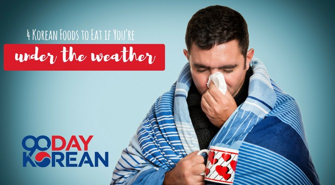 Man blowing his nose holding a mug wrapped in a blanket
