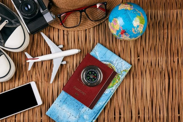 Wicker basket with shoes, camera, hat, toy airplane, toy globe, compass, map, smartphone, and passport on top