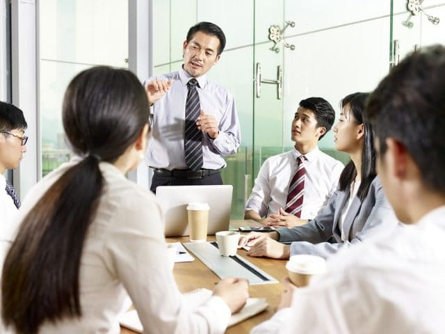 Asian Business Manager Talking To Team During Meeting