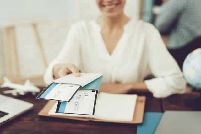 Travel Agent Holding Tickets In Travel Agency