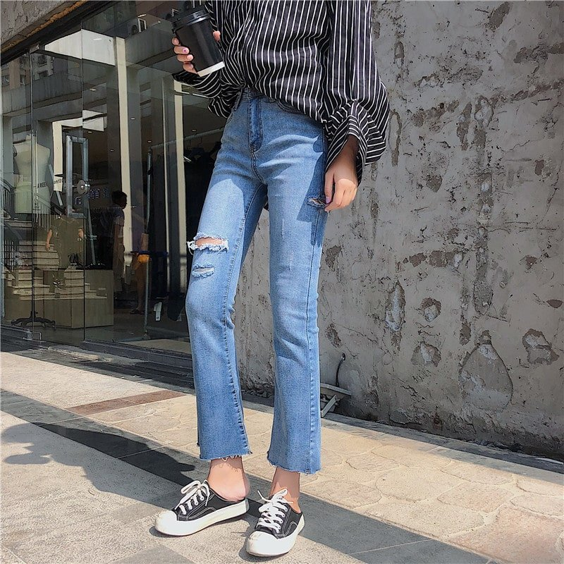 Woman with a striped shirt, ripped jeans, and black and white shoes holding a coffee cup