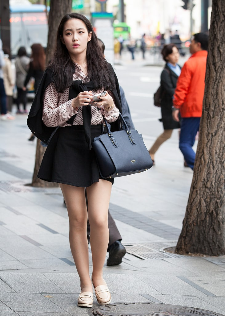 Young woman in Seoul wearing a red and white shirt, black skirt, tan shoes, and holding a black bag while walking down the street