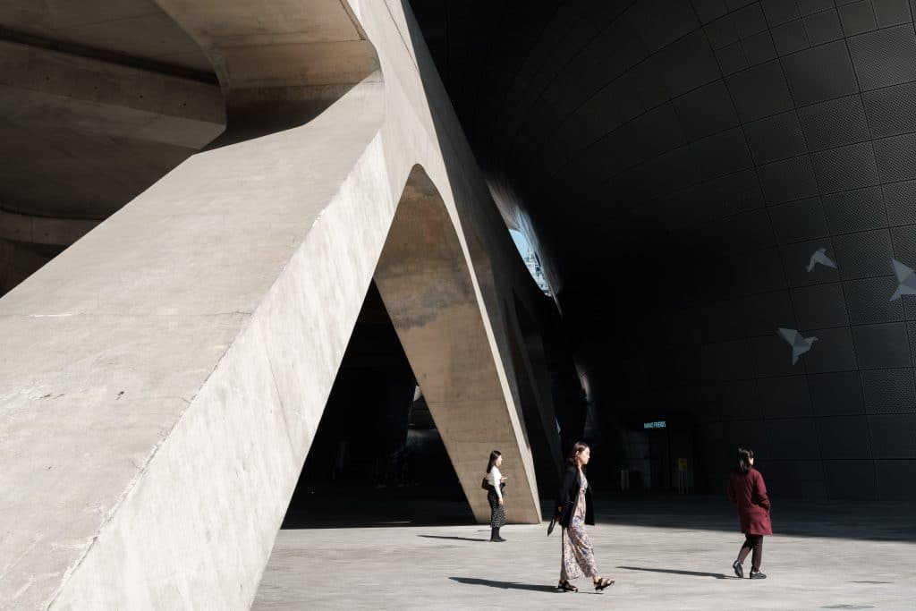 3 women walking around near a large concrete structure
