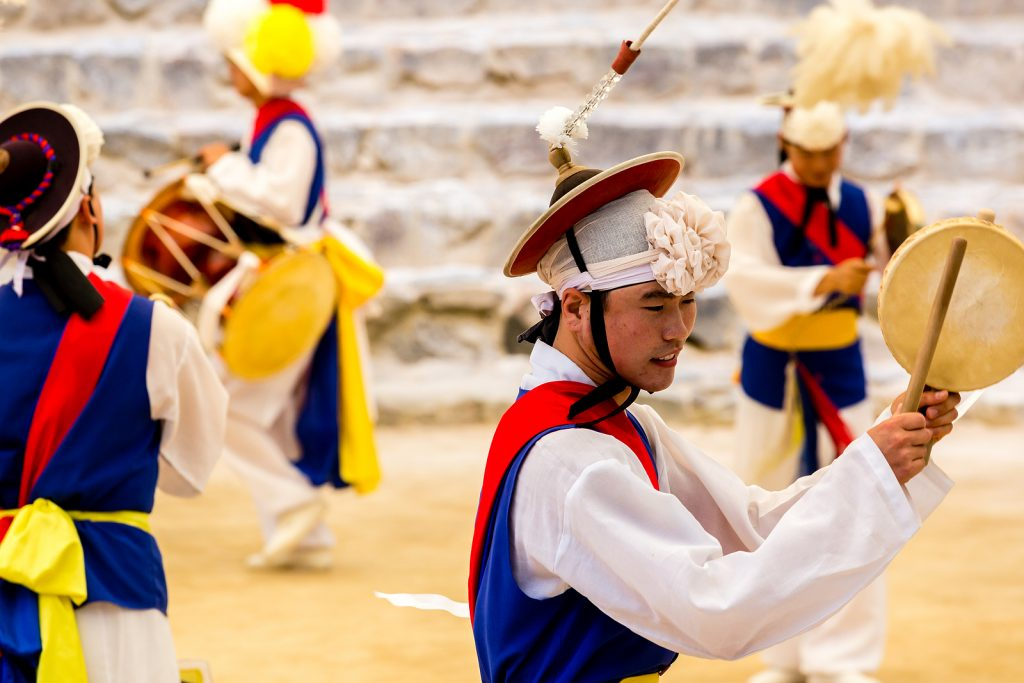 A group fo male dancers dancing and playing traditional Korean instrument