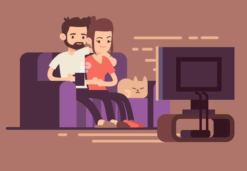 Couple watching TV with a cat sitting on a couch