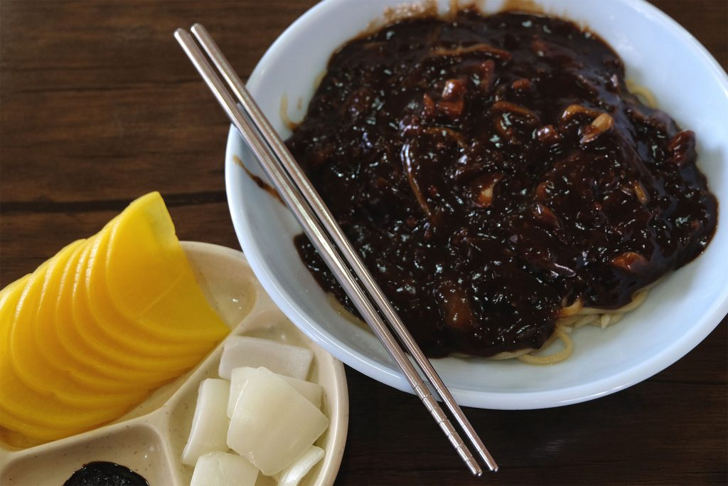 A dish made of noodles with black bean sauce. There is also a pair of chopsticks and two side dishes